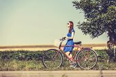image of country girl  - Redhead girl with bicycle on country road.