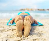 stock photo of sunbather  - Woman sunbathing on sand - JPG