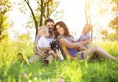 stock photo of father time  - Happy young family spending time together outside in green nature - JPG