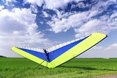 picture of glider  - Motorized hang glider over green grass ready to fly - JPG
