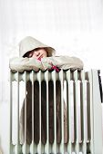 picture of freezing temperatures  - Freezing Young Girl in Winter Jacket Near a Heater.