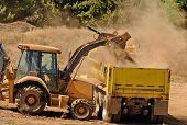 image of backhoe  - A backhoe loads duft and top soil into a 10 - JPG