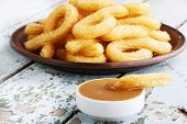 stock photo of churros  - churros sweet dessert with caramel plate on a wooden surface - JPG
