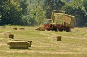 pic of hay bale  - Self contaned hay bale wagon picking up bales of alfalfa from a farm field - JPG