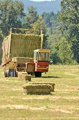 stock photo of wagon  - Self contaned hay bale wagon picking up bales of alfalfa from a farm field - JPG