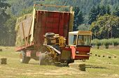 stock photo of alfalfa  - Self contaned hay bale wagon picking up bales of alfalfa from a farm field - JPG