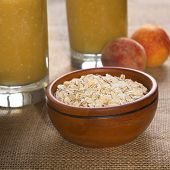 image of oats  - Bowl full of rolled oats with peaches and glasses of fruit milkshakes mixed with oatmeal in the back photographed with natural light  - JPG
