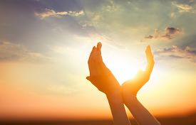 stock photo of hand god  - hands holding the sun with sunset on backgound  - JPG