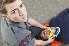 stock photo of ambulance  - Paramedic employee with ambulance in the background - JPG