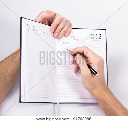 isolated hand holding pen and writing in diary