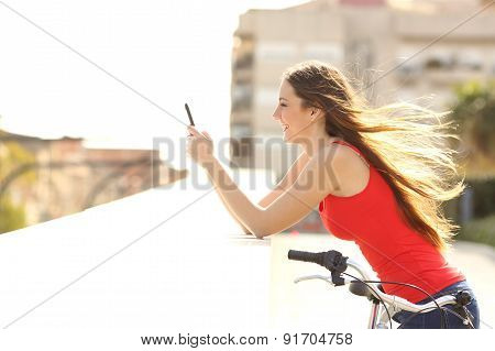Profile Of A Teen Girl Using A Mobile Phone In A Park