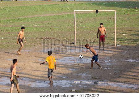 AMARAPURA, MYANMAR, JANUARY 18, 2015: Burmese young men are playing football near the Ubein bridge in Amarapura, Myanmar (Burma).