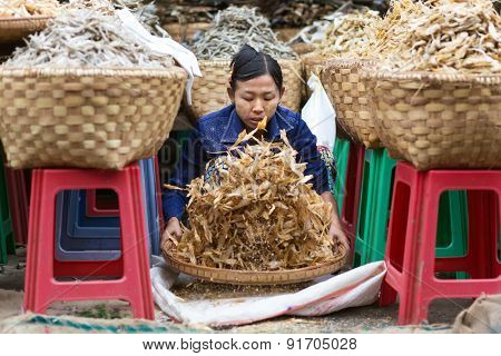 MANDALAY,MYANMAR,JANUARY 17, 2015: A seller is sieving the dry fish in the central street market of Zegyo, in Mandalay, Myanmar (Burma).
