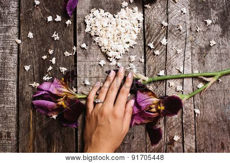 Heart Shape Of White Lilac Flowers And Hand With Ring On Wood Table