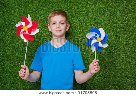 Boy holding pinwheels over grass