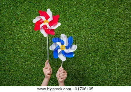 Hand holding pinwheels over grass