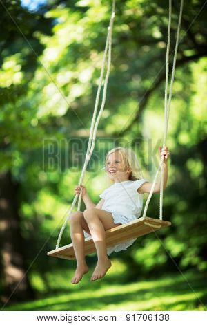 Little girl on a swing outdoors