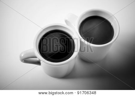 Two Cups Full Of Coffee Stand On A Table