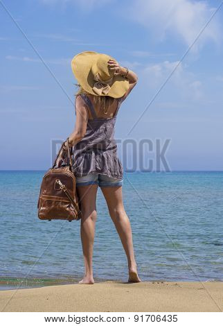 Woman with leather travel bag on the beach going on holidays