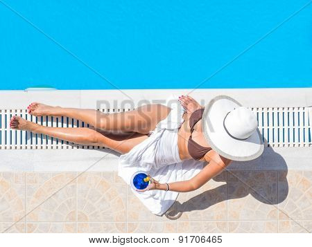 Young woman in bikini with a straw hat by the swimming pool