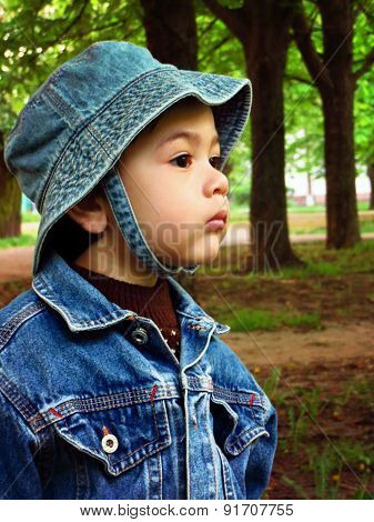 Portrait of a baby boy in a denim jacket and a panama hat