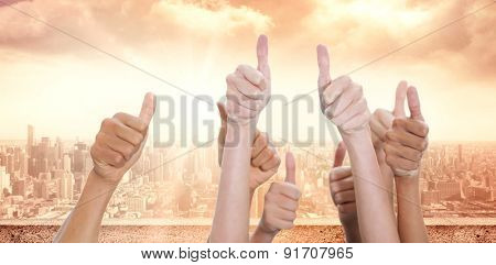 Hands up and thumbs raised against sun shining over city