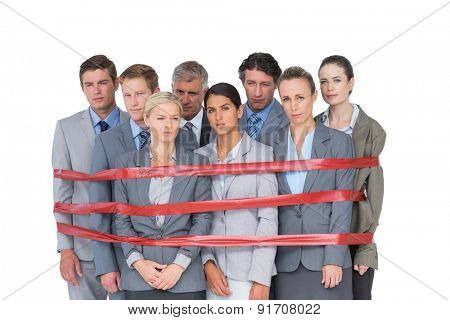 Upset business team fastened with adhesive tape on white background