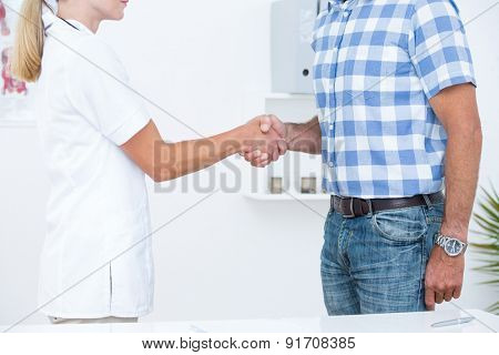 Patient shaking hands with doctor in medical office