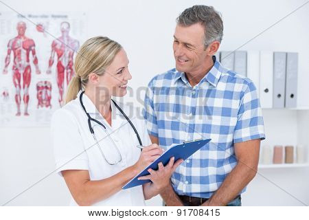 Doctor showing clipboard to her patient in medical office