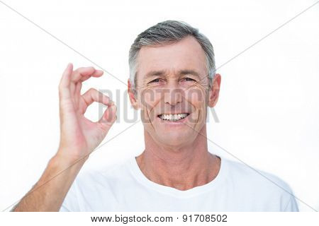 Smiling patient looking at camera and gesturing ok sign in medical office