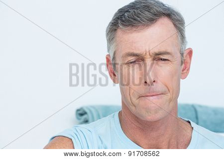 Patient with pain looking at camera in medical office