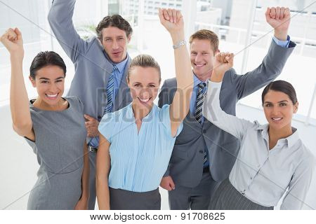 Excited business team cheering at camera in the office