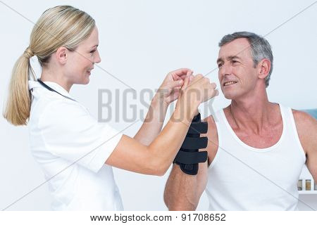 Doctor examining a man wrist in medical office