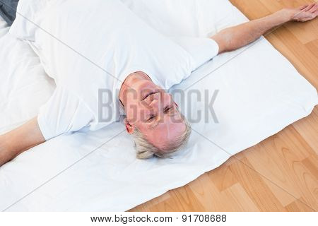 Old man relaxing with open eyes in gym