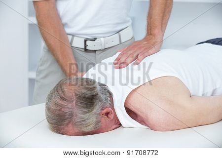 Physiotherapist doing shoulder massage to his patient in medical office