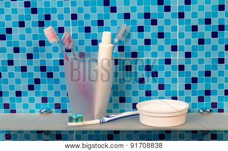 Toothbrushes and dentifrice on a shelf