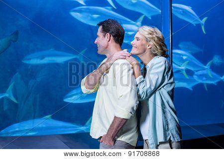 Happy couple looking at fish tank at the aquarium