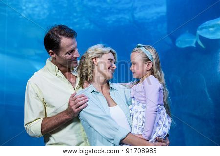 Happy family smiling at each other beside the fish tank