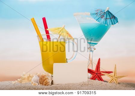 Coctails and blank paper in the sand