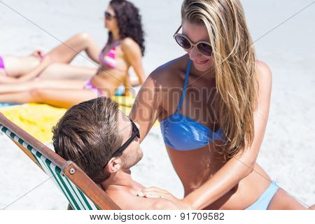 Happy couple relaxing on the desk chair at the beach