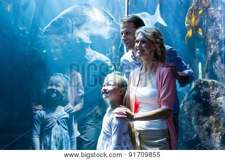Happy family looking at in a tank at the aquarium