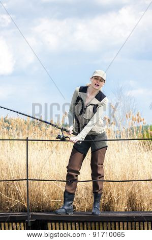 woman fishing on pier at pond