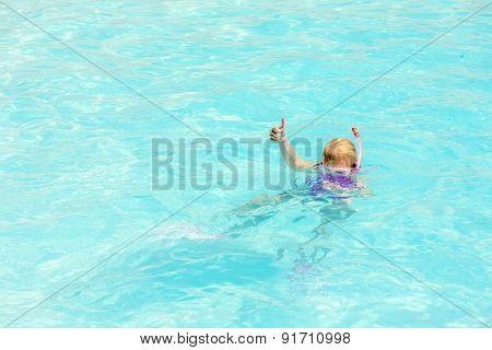 little girl snorkeling in swimming pool
