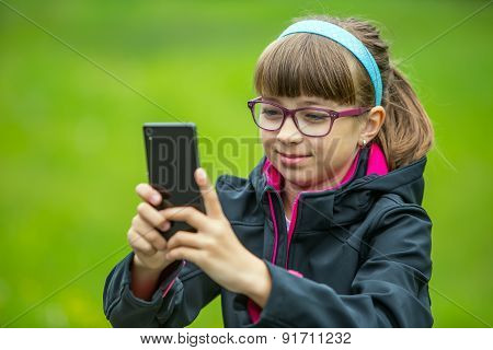 Close portrait Little girl with mobile phone. Little girl with standing and texting with the phone