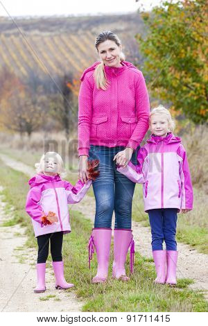 Mother and her daughters in autumnal nature