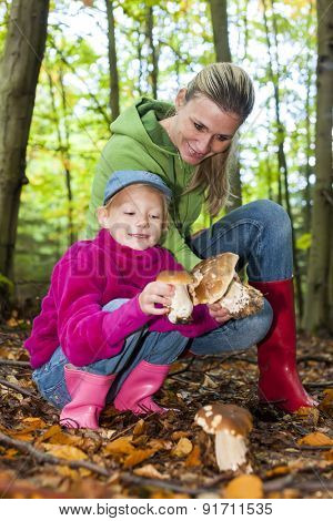 mother with her daughter doing mushroom picking