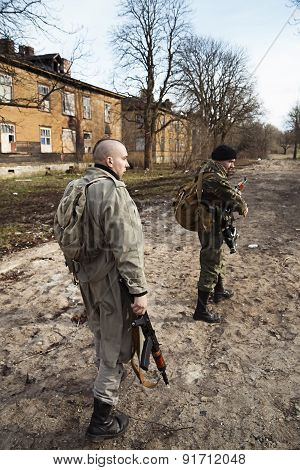 Two Armed Men Looking Around In The Village