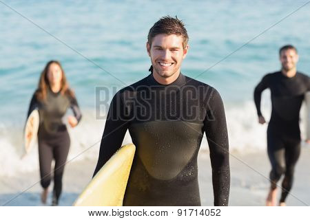 Group of friends on wetsuits with a surfboard on a sunny day at the beach