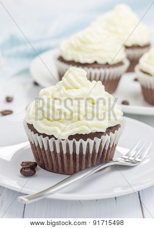 Chocolate Cupcakes With Ricotta Cheese Frosting On The White Plate