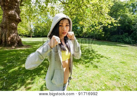 Portrait of determined fit woman practicing boxing at park